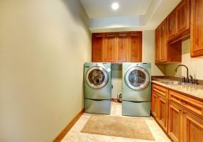 Rectangle laundry room with wooden cabinets and modern shiny appliances